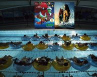 Public en piscine regardant un film