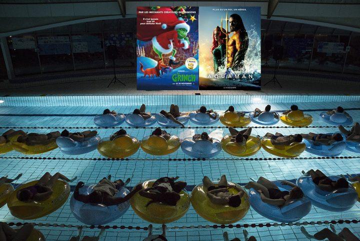 Public en piscine regardant un film