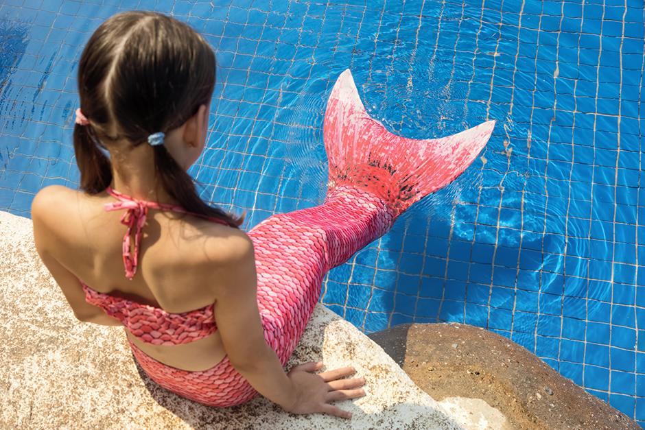 Petite fille sirène au bord du bassin de la piscine