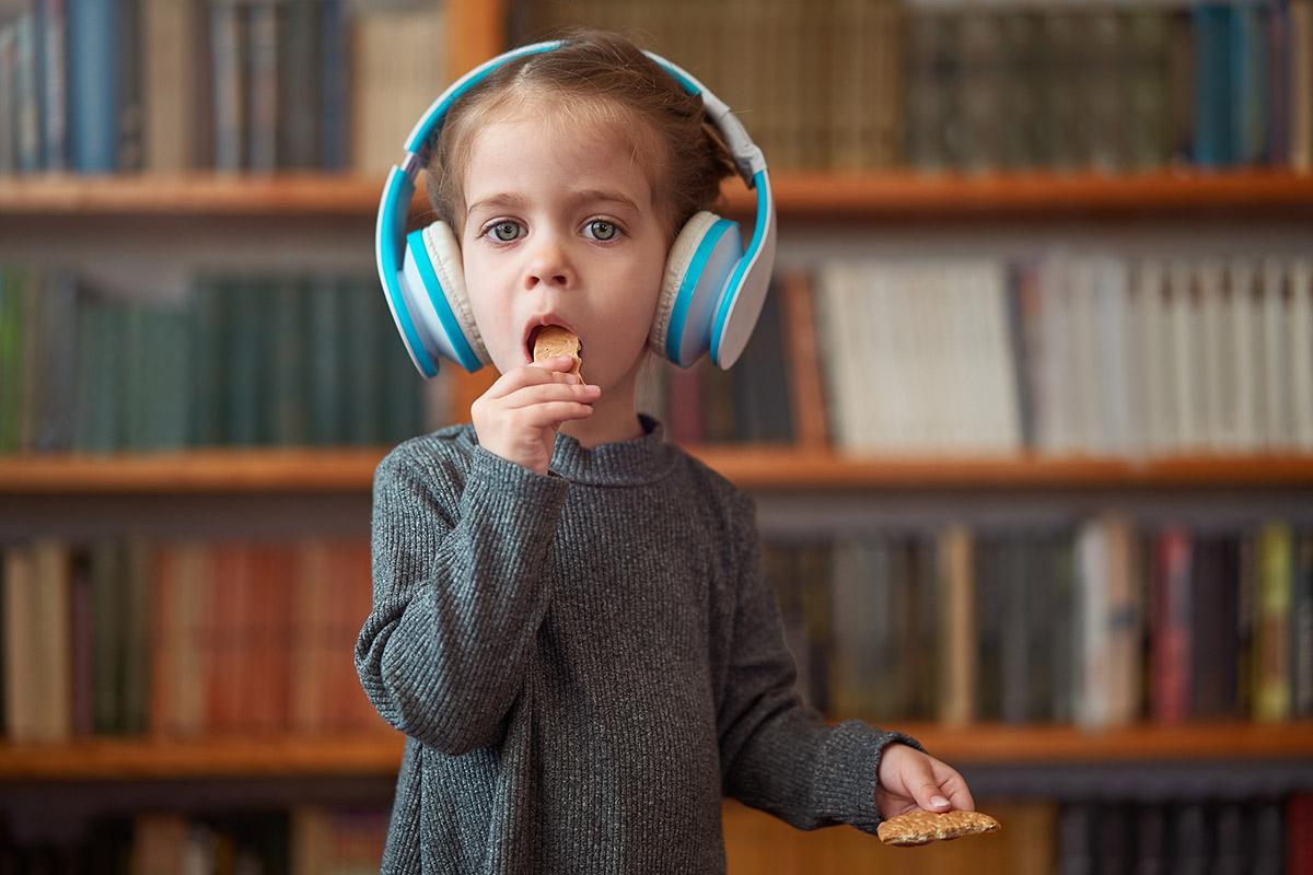 Enfant de 3 ans avec un casque audio sur les oreilles en train de manger un gâteau