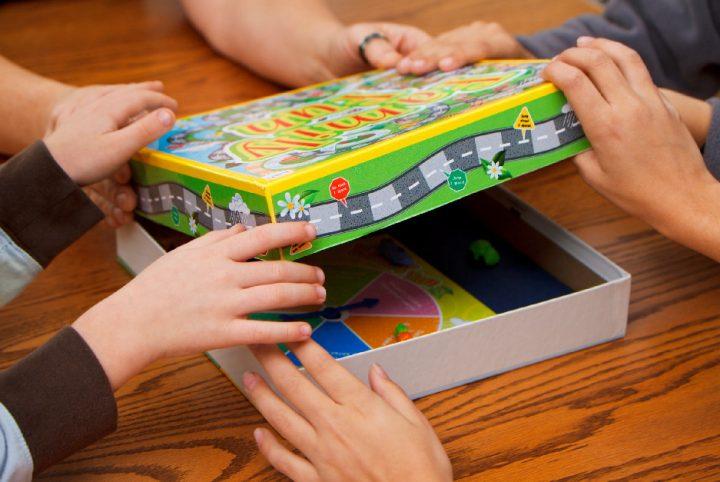 Photo de mains ouvrant une boîte de jeux de société
