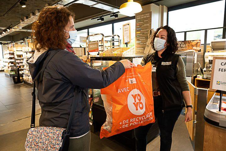 Habitante qui donne son sac orange Yoyo à une commerçante