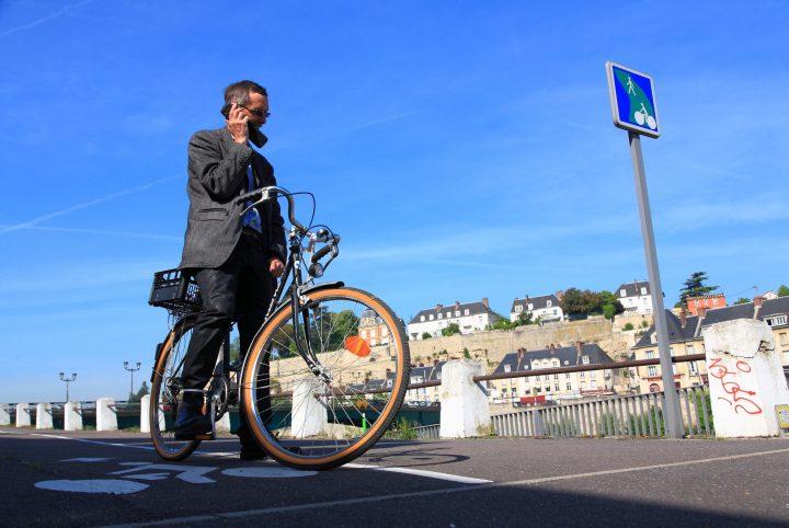 Homme en costume en vélo à l'arrêt sous un panneau de signalisation