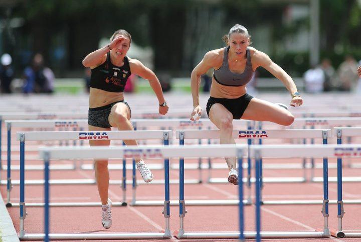 2 athlètes féminines en plein effort dans une course de haies.